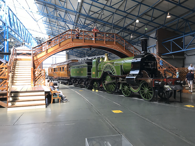 Opal standing on a bridge over a green locomotive in the UK National Rail Museum