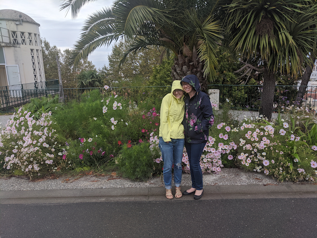 Kerry and Jo in front of a flower bed hiding from the rain